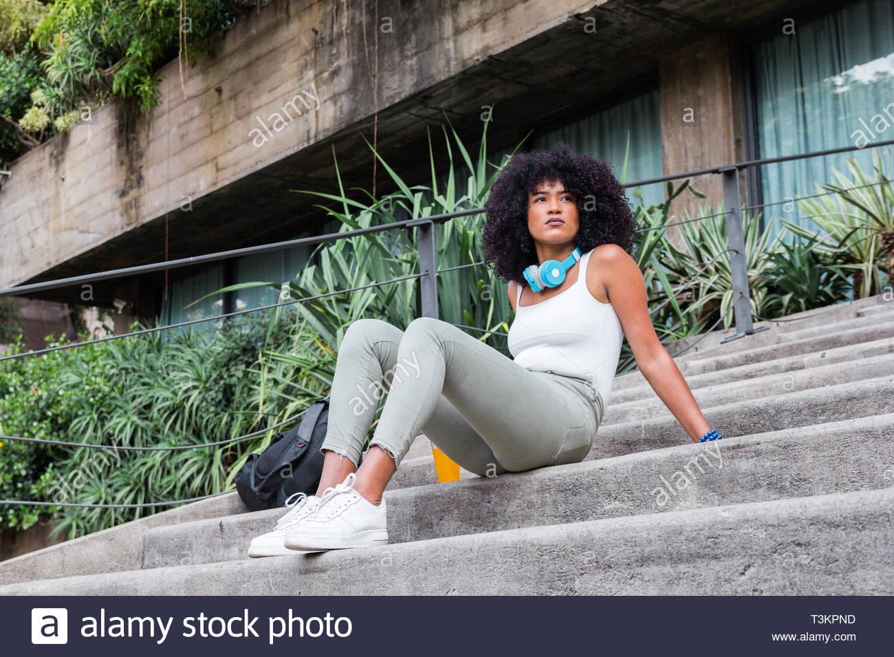 Young student hipster tourist girl with afro hairstyle sitting in the steps outside. In contemplation, relaxing and taking a break. - Stock Image