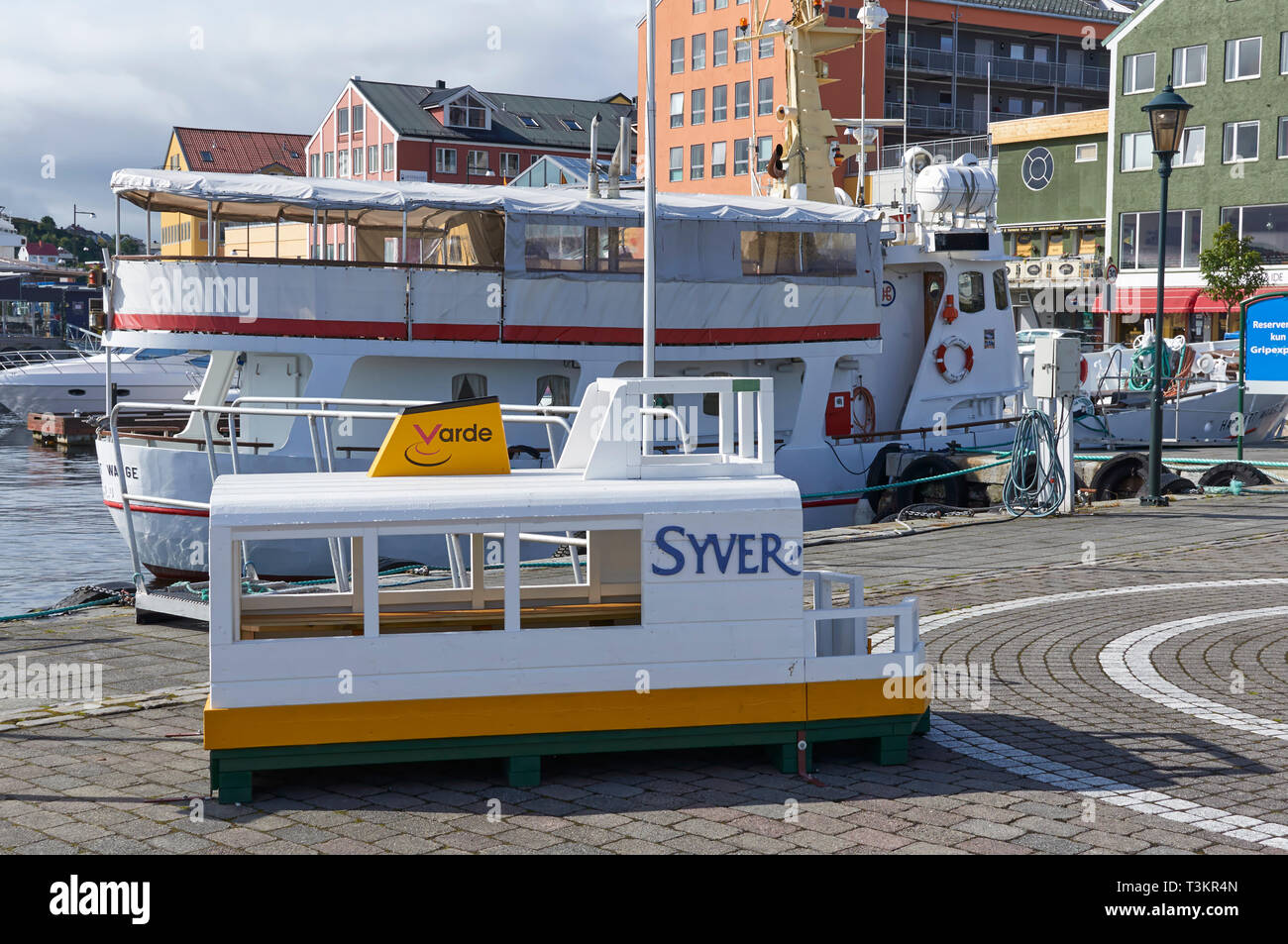 A small Childs Boat seat on the Ferry Quay at Kristiansund, with a Passenger Vessel tied up on the quayside on a Summers Day. Norway. - Stock Image