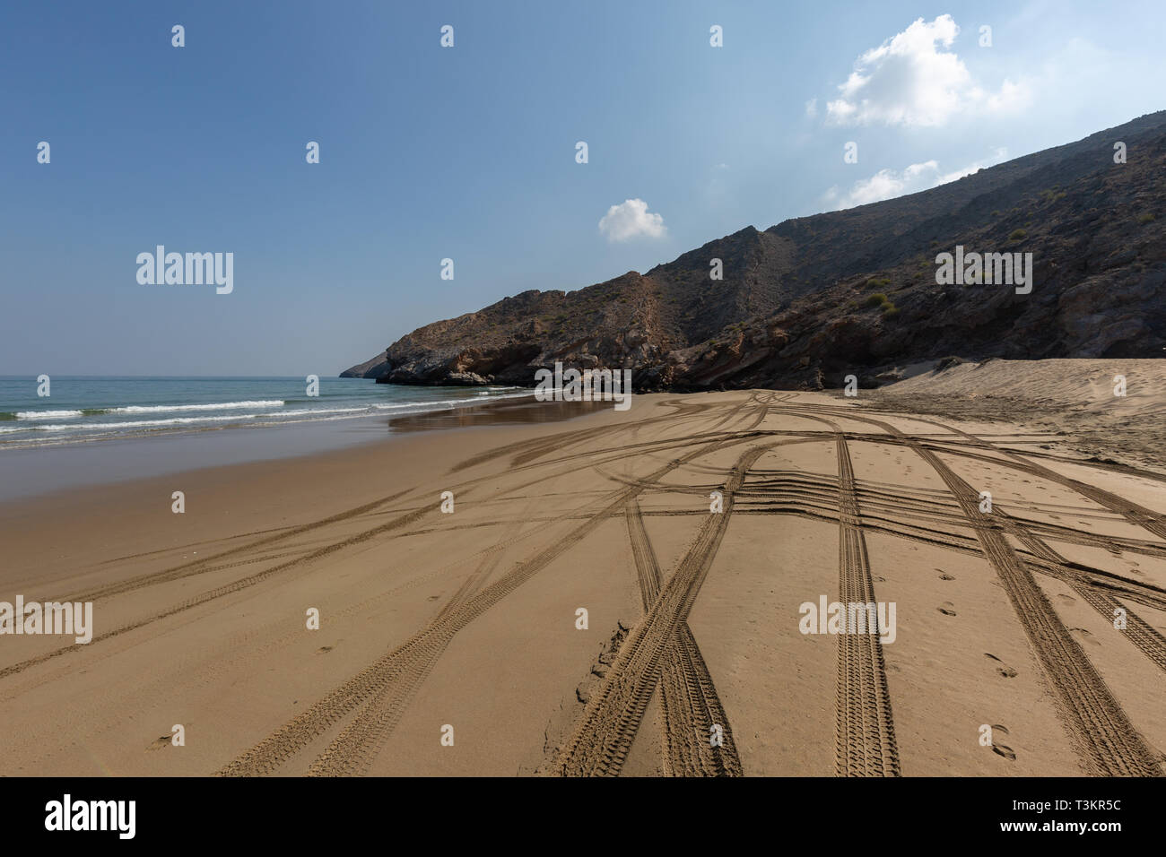 Empty Yiti Beach in the morning, tire tracks on the sand near Muscat - Sultanate of Oman - Stock Image