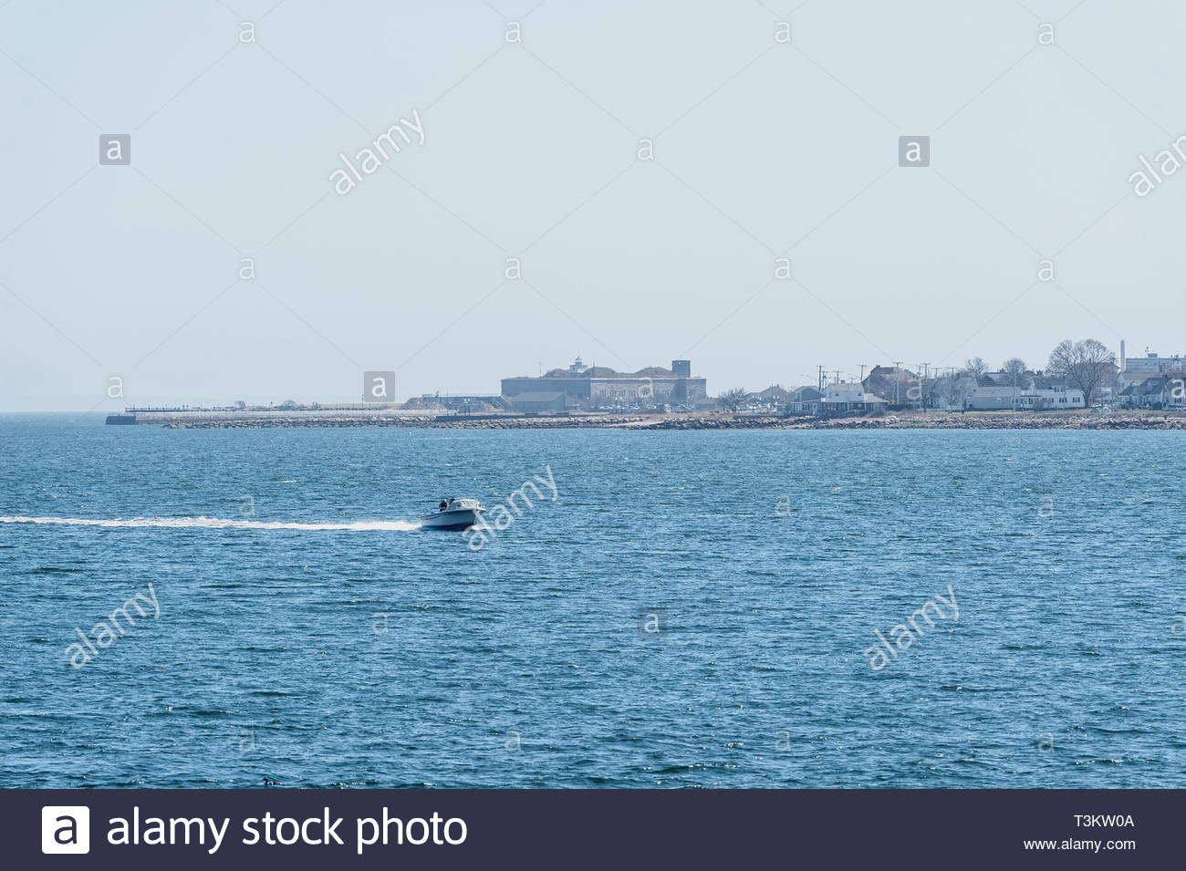 New Bedford, Massachusetts, USA - April 6, 2019: Powerboat zipping across New Bedford outer harbor on hazy afternoon with Fort Taber in background - Stock Image