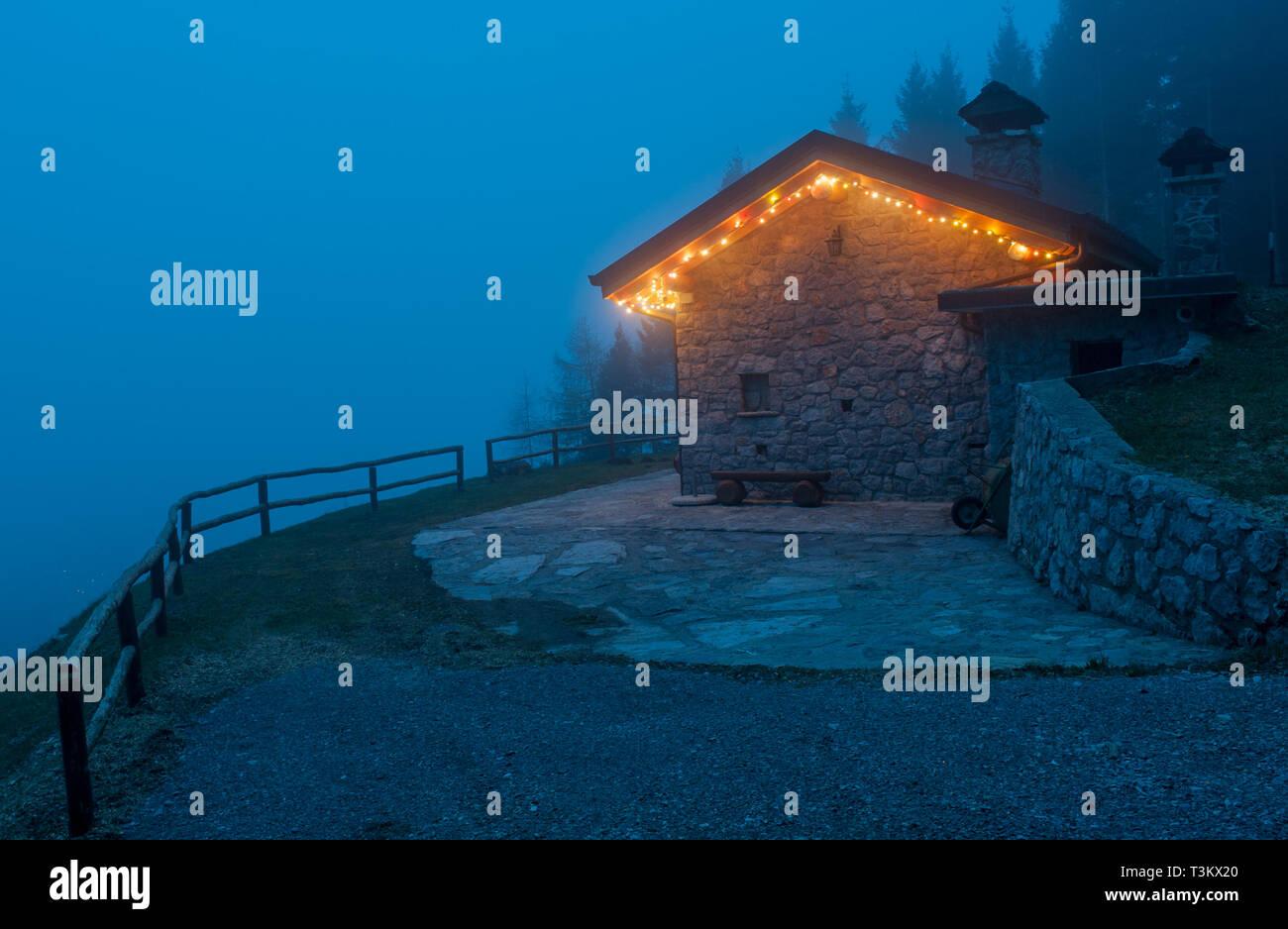 mountain retreat illuminated for new year - Stock Image