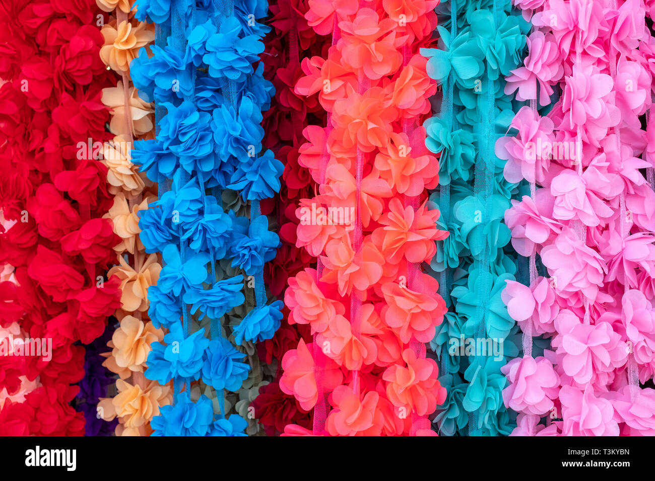 JERUSALEM, ISRAEL - APRIL 8, 2019: A row of vividly colourful artificial flowers hangs outide a shop on Jaffa Road. - Stock Image