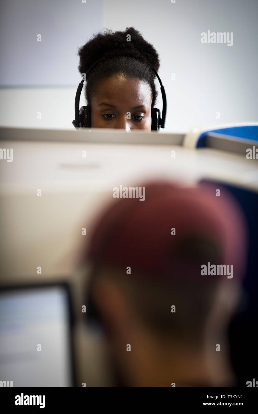 A member of staff working in the RSVP Manchester call centre. The company employs people in acting and entertainment management to take calls at their offices in Salford Quays, Manchester. The company opened the office in October, 2016. - Stock Image