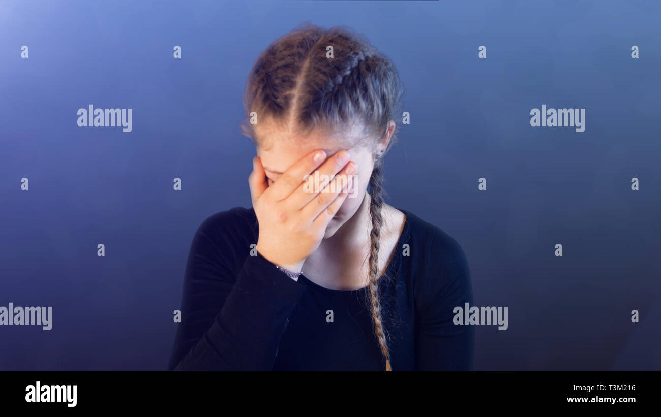 Teenage girl with pigtails, being attacked by social media, creating emotional stress - Stock Image