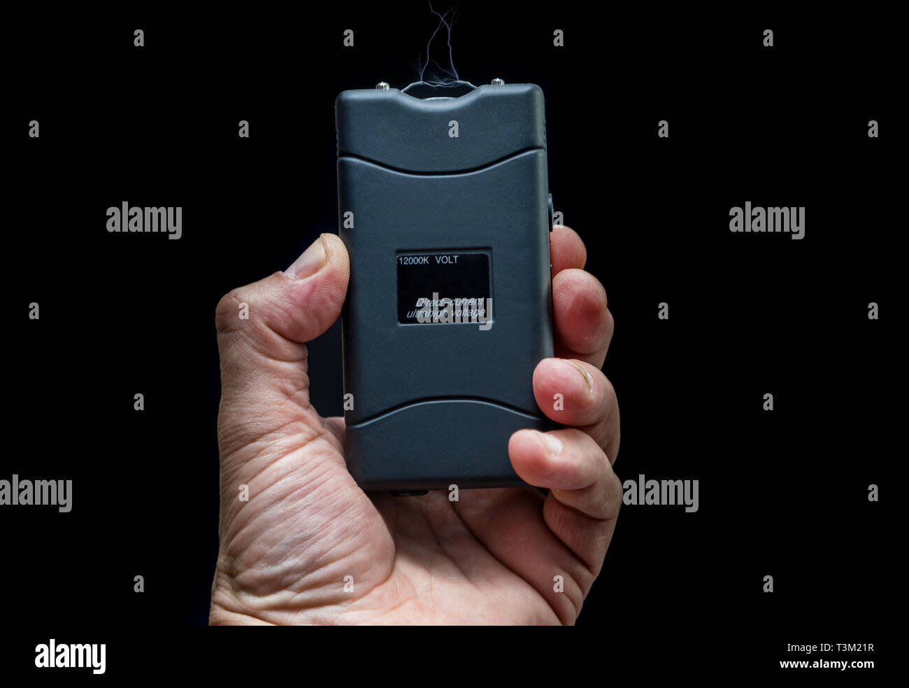 Hand holds a stun gun in front of black background - Stock Image
