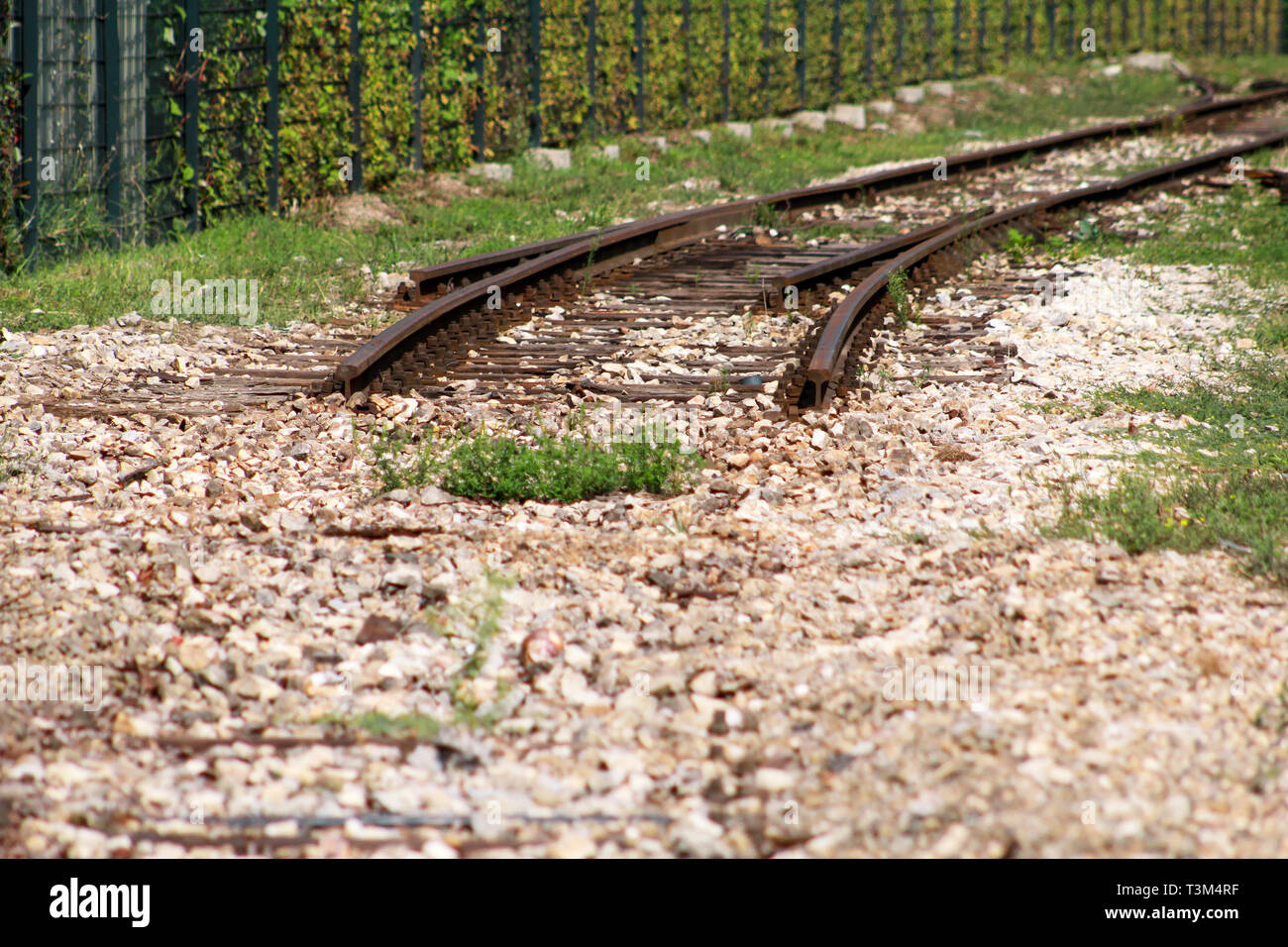 Old railway track in urban city. Vintage railroad. Close view of old railroad tracks with worn ties and gravel ballast in the summertime. - Stock Image