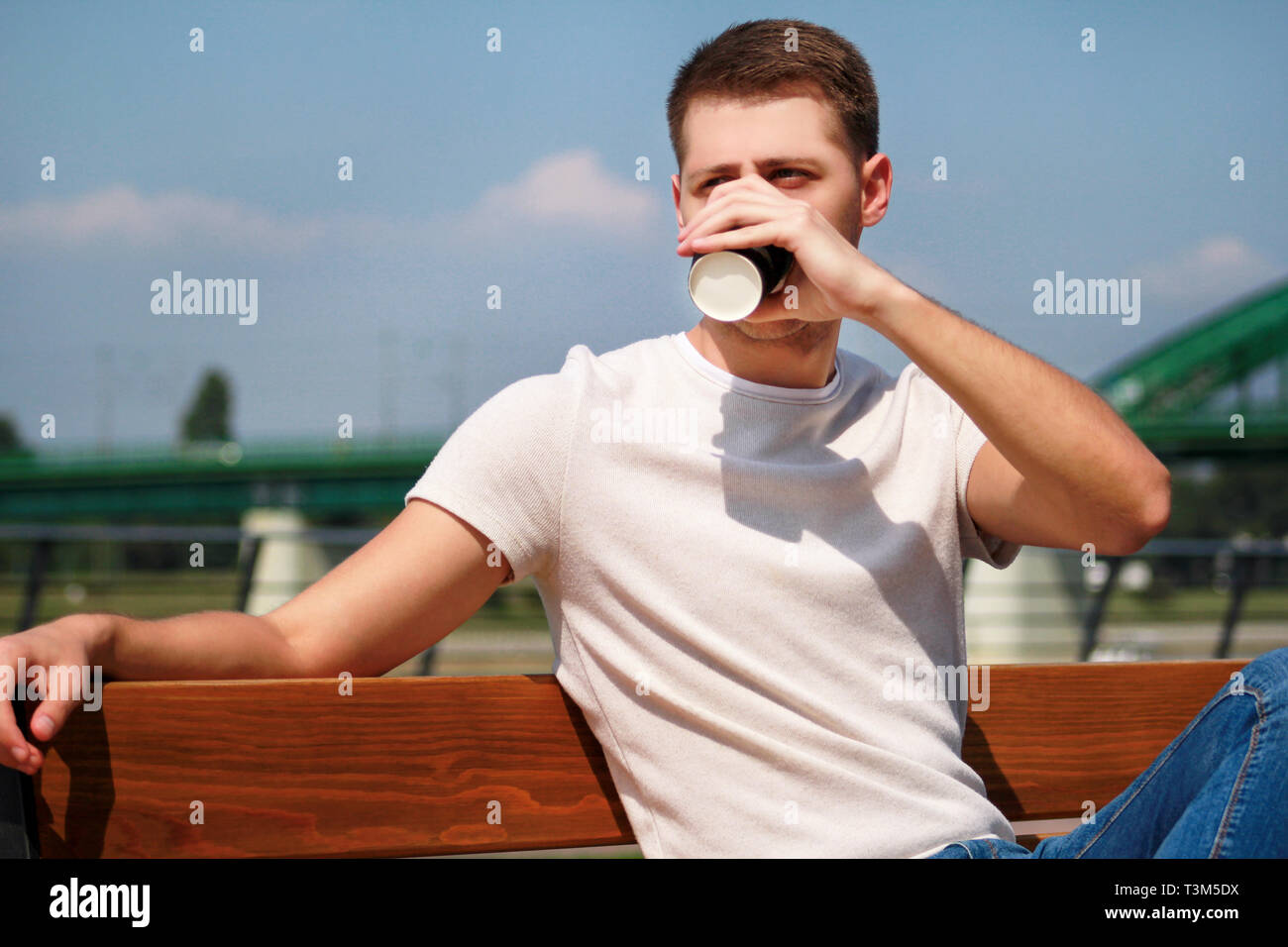 Handsome guy sitting on a bench on a pier and drinking coffee to go. Taking a break from city rush. Background scenery bridge, river, pier. - Stock Image