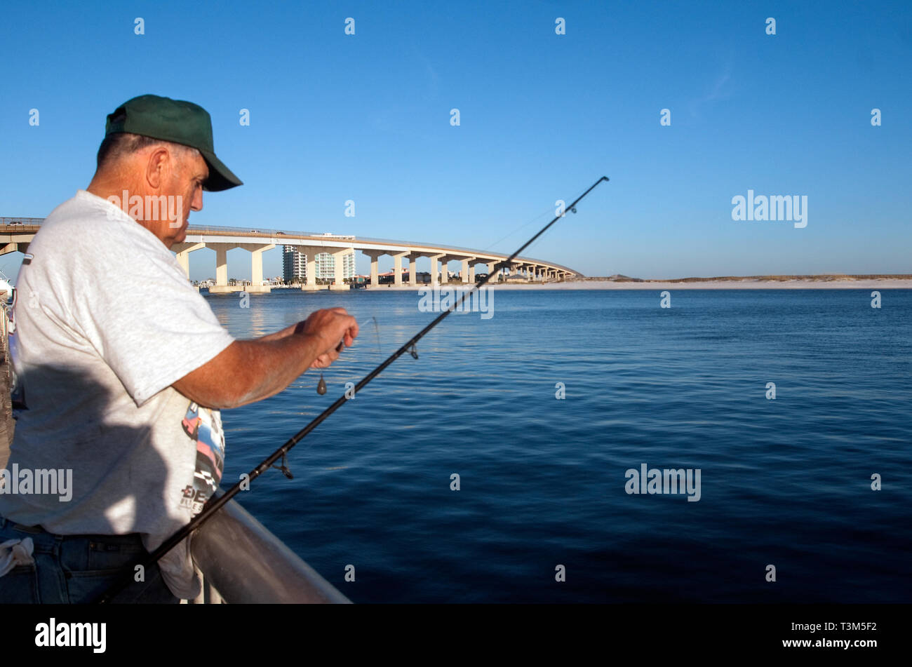 A fisherman baits his hook at Florida Point fishing pier Nov. 12, 2009 in Orange Beach, Alabama. Stock Photo