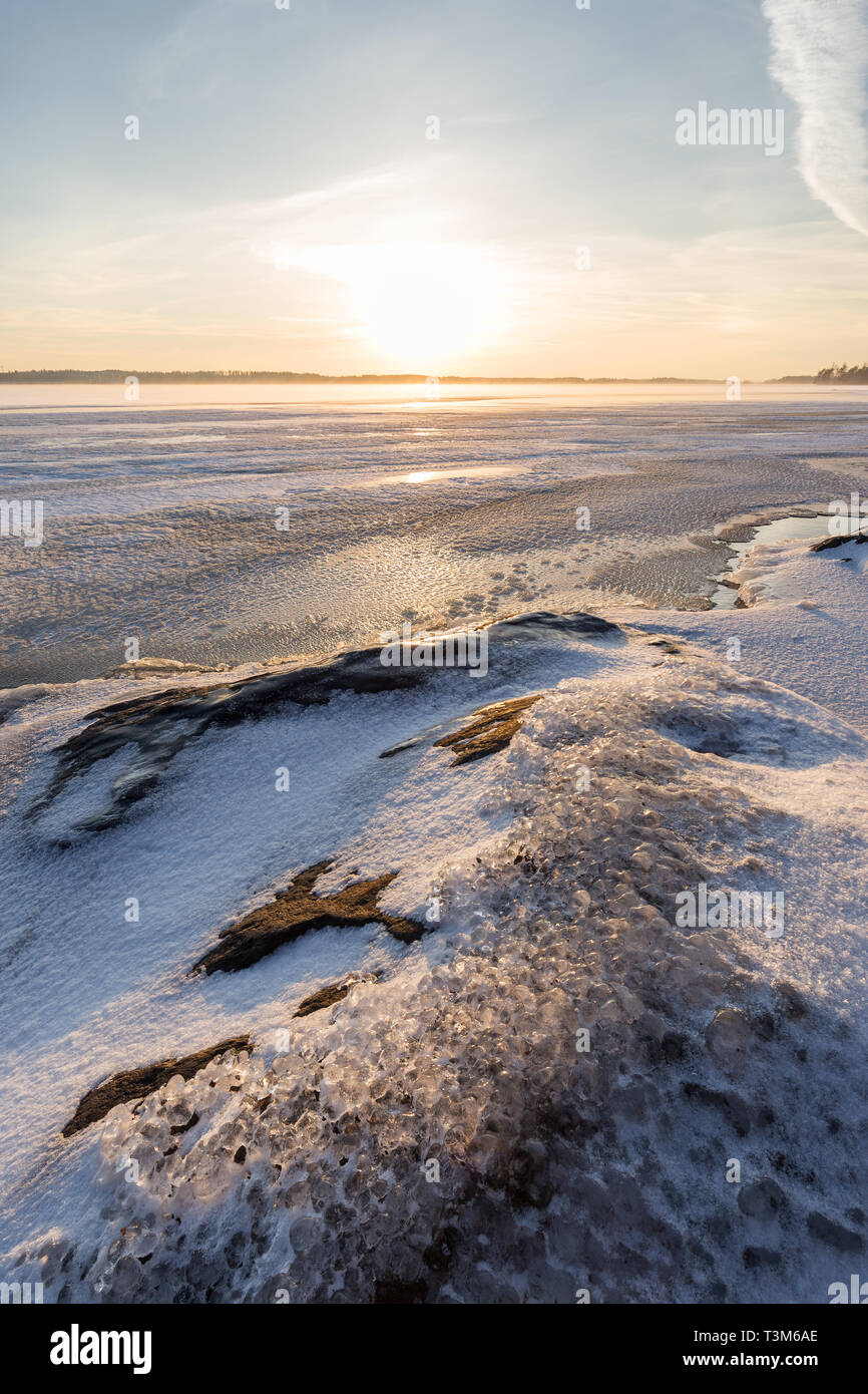 Serene landscape of ice, snow, icy rock and frozen and snowy lake in Finland in the winter at sunny morning. - Stock Image