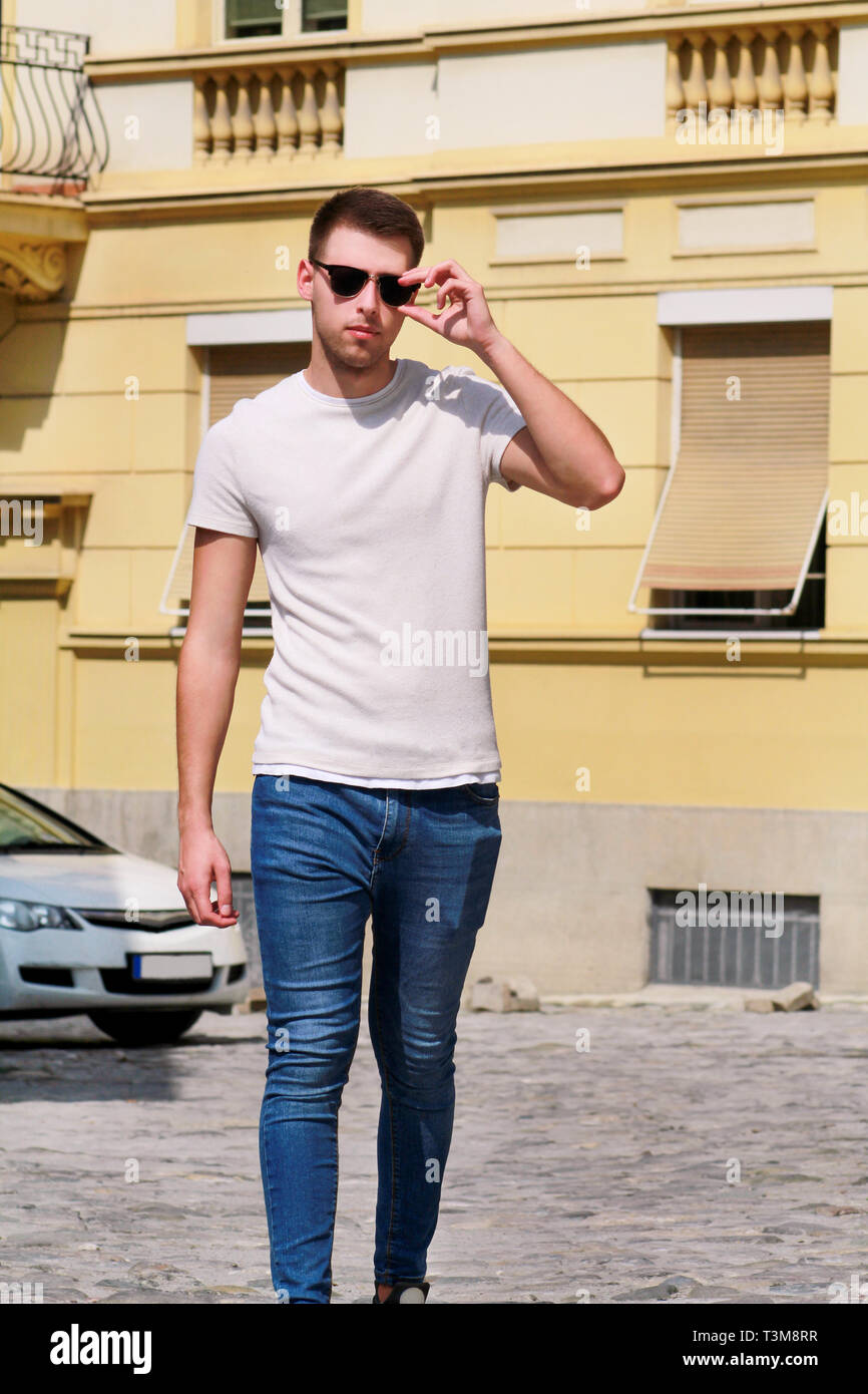 Portrait Of Handsome Young Man With Sunglasses Is Posing And Walking On Urban City Street Male Model Photo Shoot Outdoors Urban Fashion Boy Stylish Stock Photo Alamy