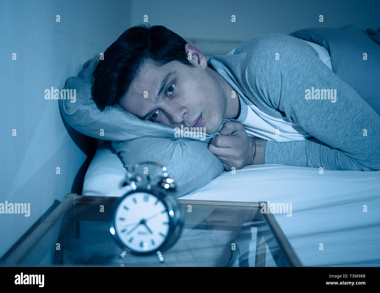 Sleepless and desperate young caucasian man awake at night not able to sleep, feeling frustrated and worried looking at clock suffering from insomnia  - Stock Image