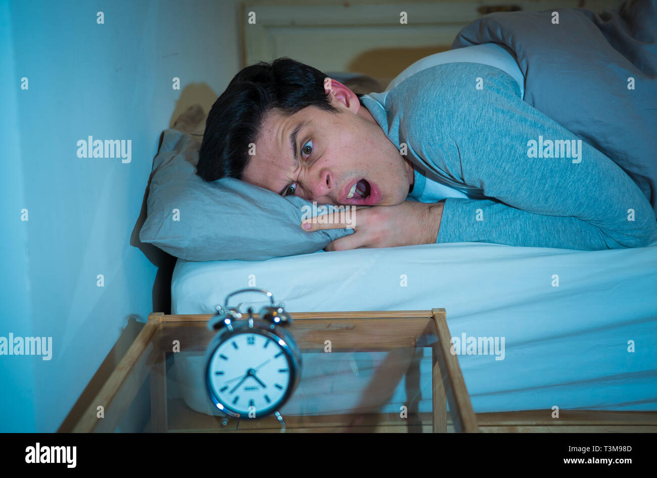 Sleepless and desperate young man awake at night not able to sleep, feeling frustrated and worried looking in distress at clock suffering from insomni - Stock Image