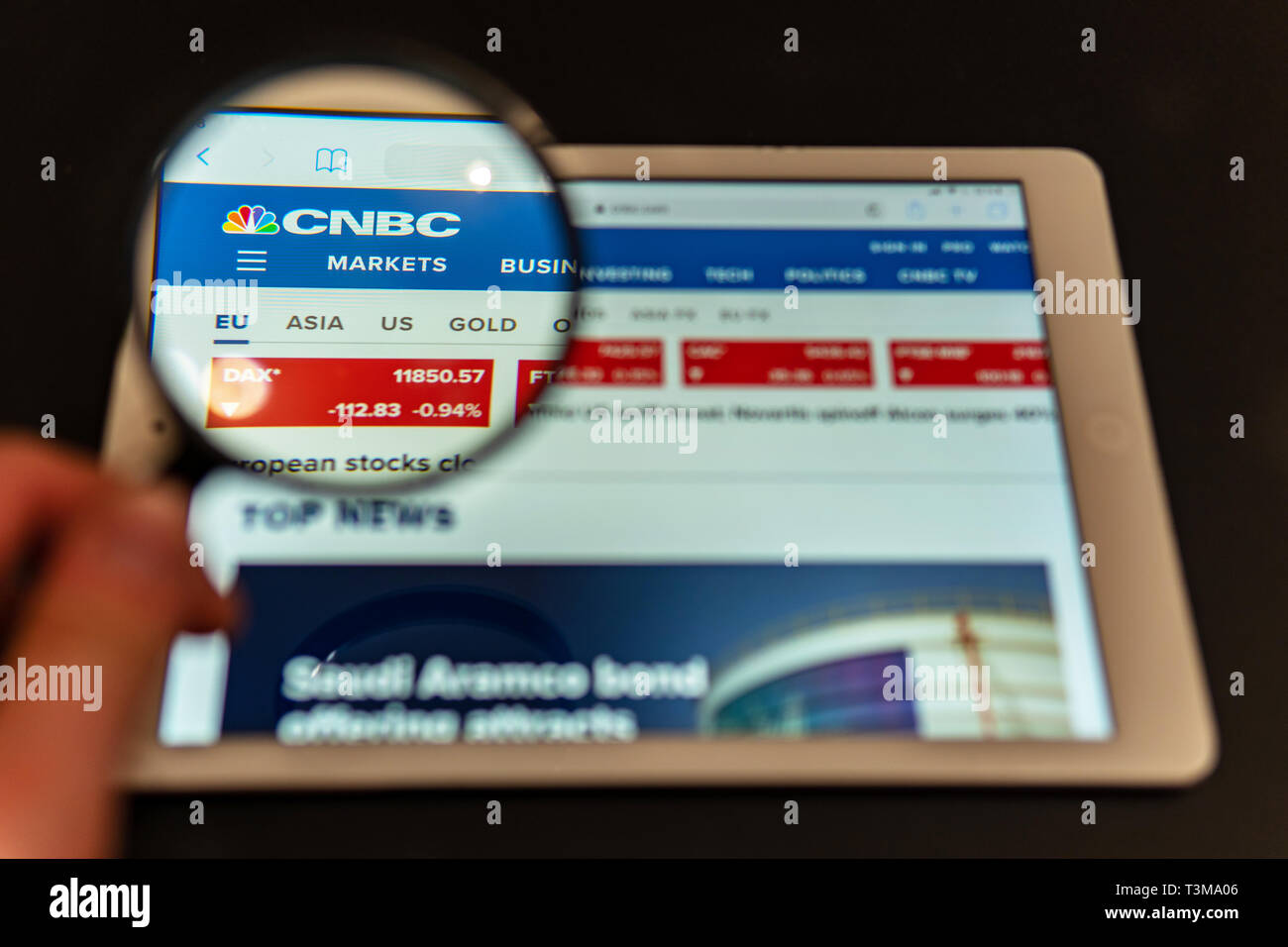 CNBC News website homepage on the tablet screen. CNBC News channel logo visible  through a magnifying glass. Marketing concept - Stock Image