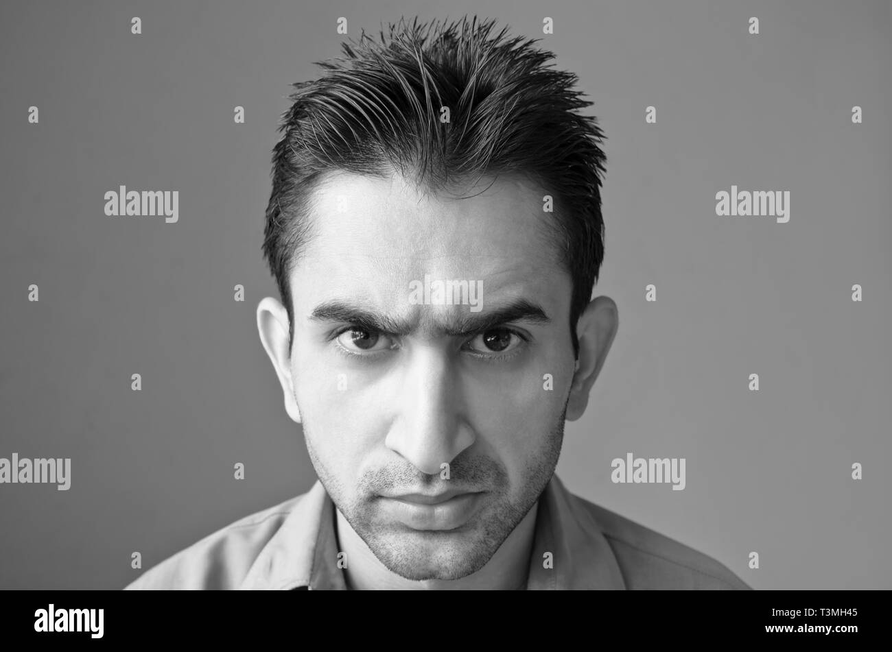 Black and white portrait of angry young man - Stock Image