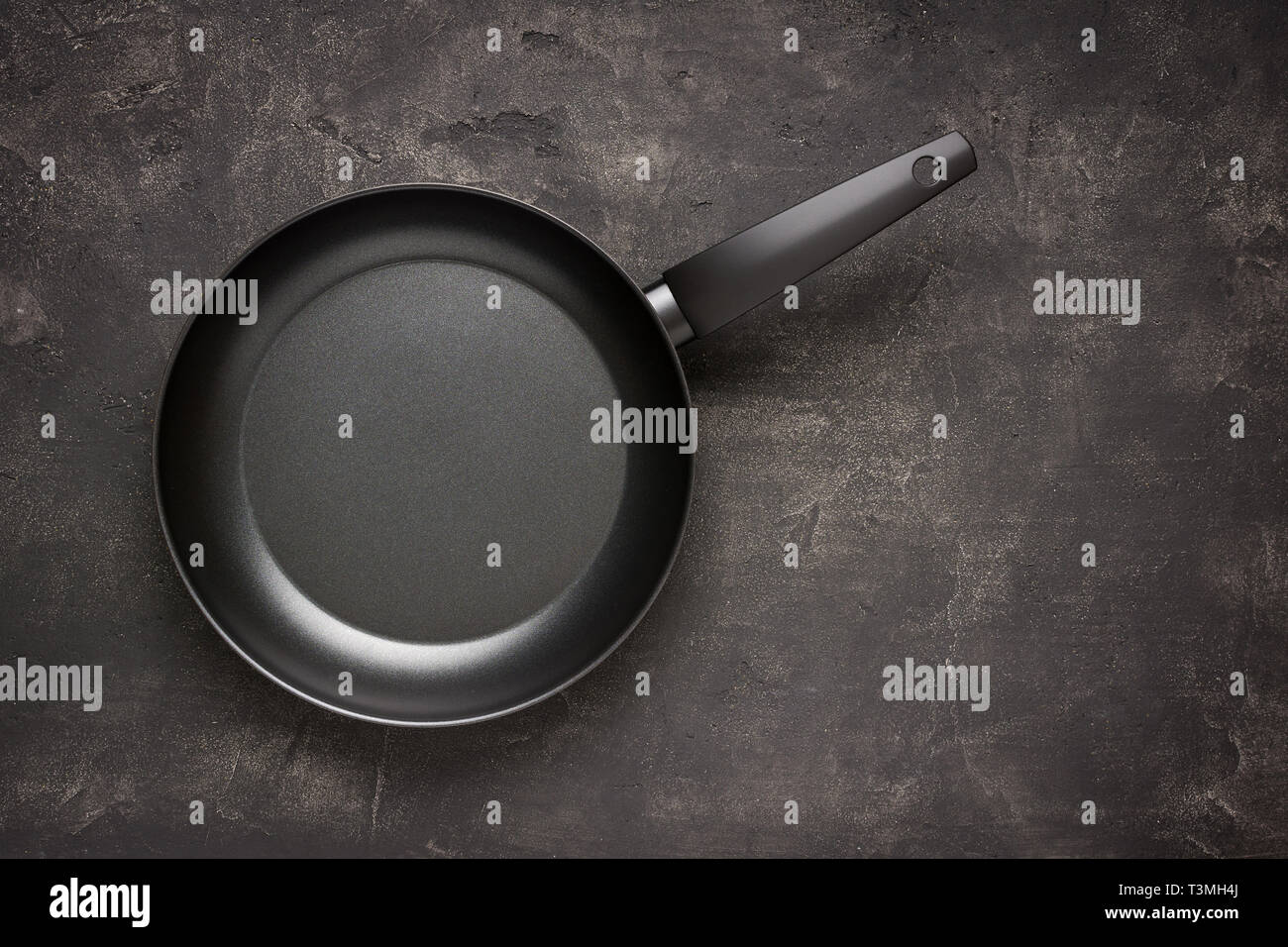 Empty Frying Pan Black on Dark Stone Surface. Culinary Background. Stock Photo