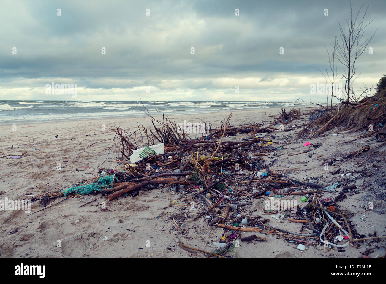 Polluted beach in the North Poland Different kind of waste castaway after a sea storm Selective focus - Stock Image