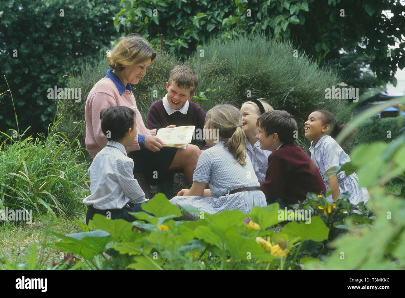 A small class of children listening to a story read by their teacher. England, UK - Stock Image