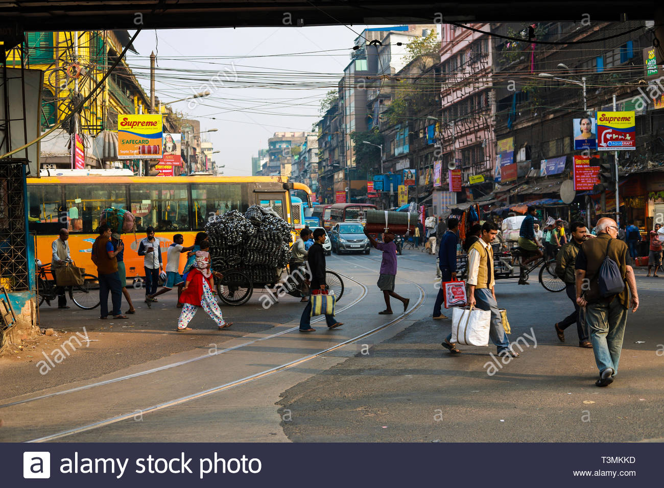 People walking on streets of kolkata and crossing busy road full of traffic - Stock Image