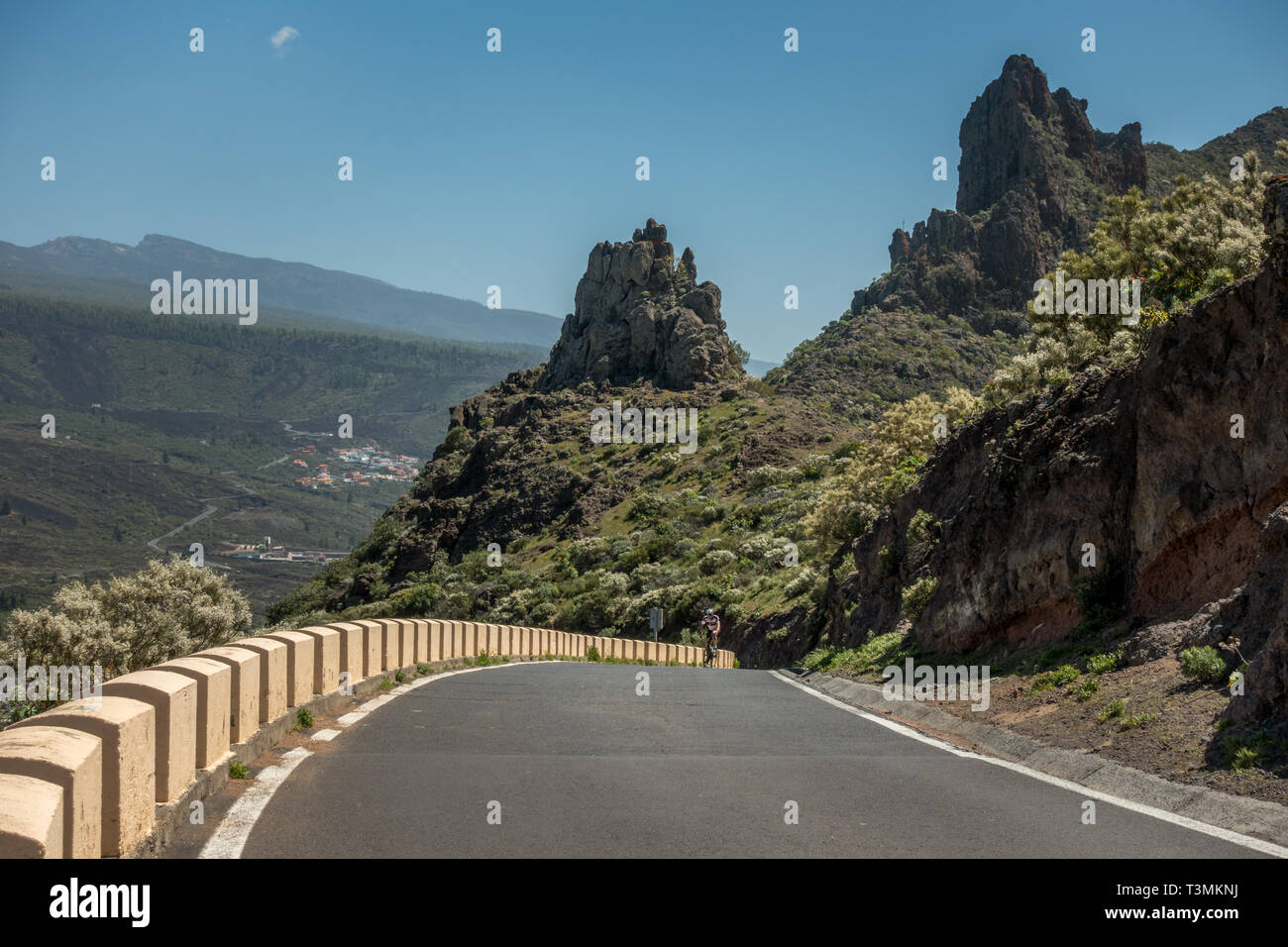 Cyclist on a road bike cycling up the steep road to the Mirador de Cherfe on the TF-436 road from Santiago del Teide. Tenerife - Stock Image