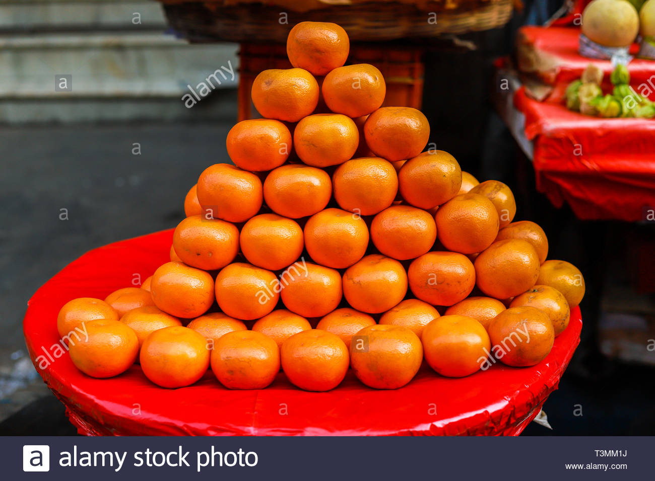 A background of fresh oranges on a market - Stock Image