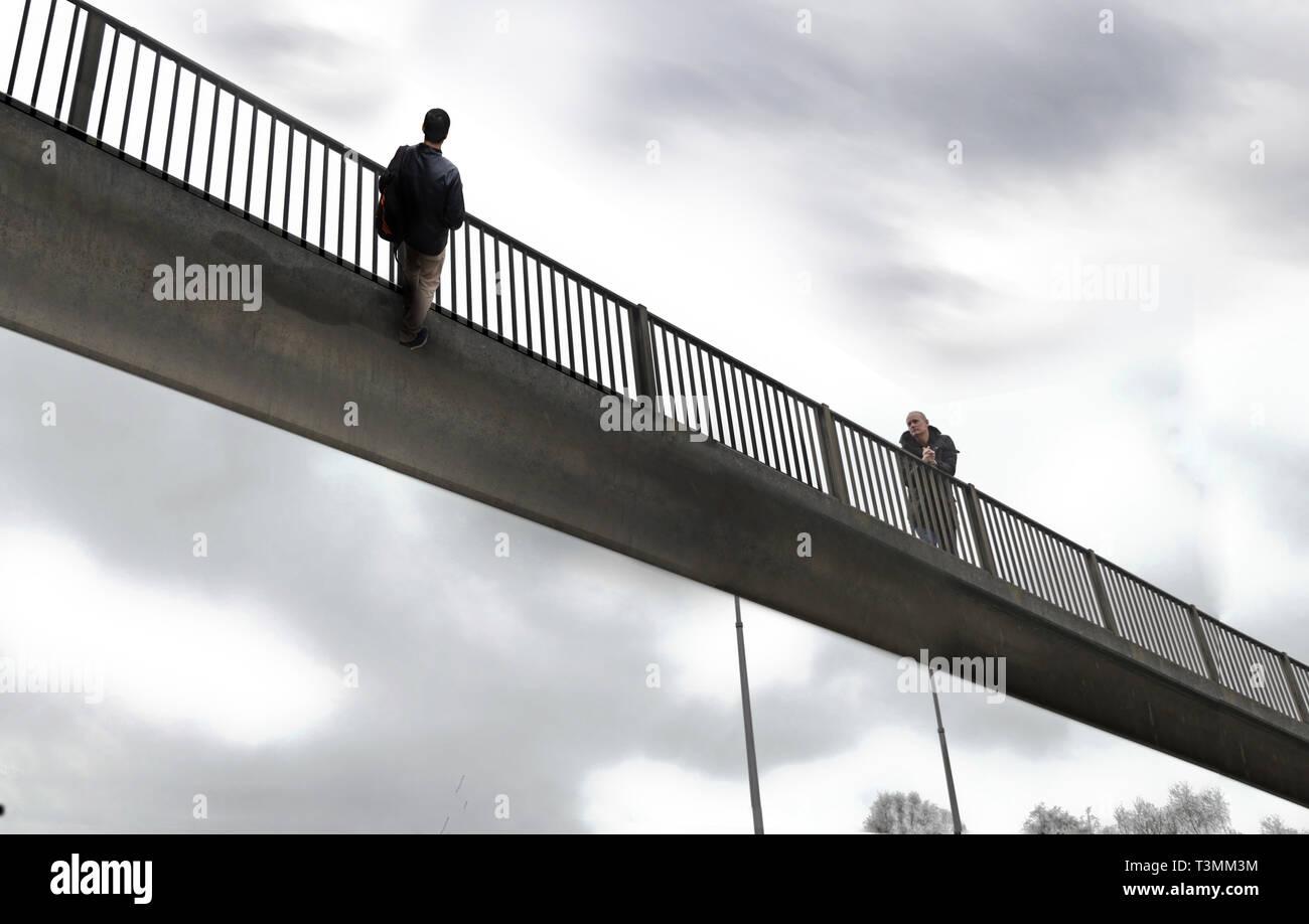 Reality-defying people standing on bridge optical illusion, UK. Stock Photo