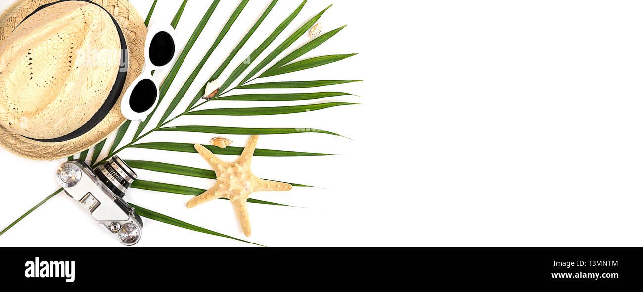 9d664456 Flat lay traveler accessories: tropical palm leaf, retro camera, straw hat,  fashion sunglasses, seashells, starfish on white background. Travel, summe