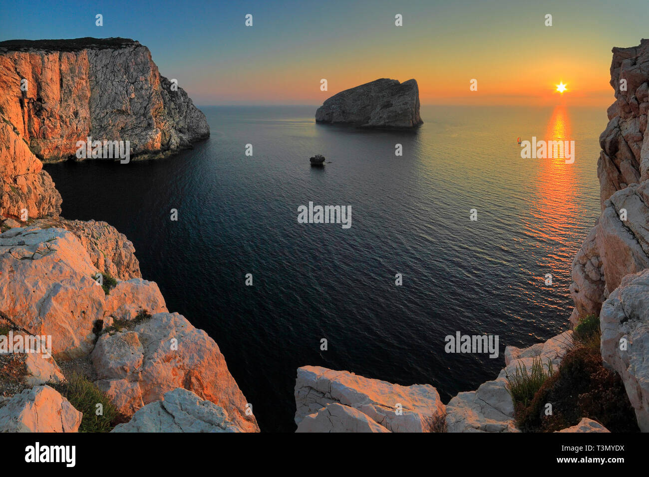 A view at sunset of the huge vertical walls of limestone of the cliffs of Capo Caccia, a wonderful promontory on the western coast of Sardinia in Ital - Stock Image
