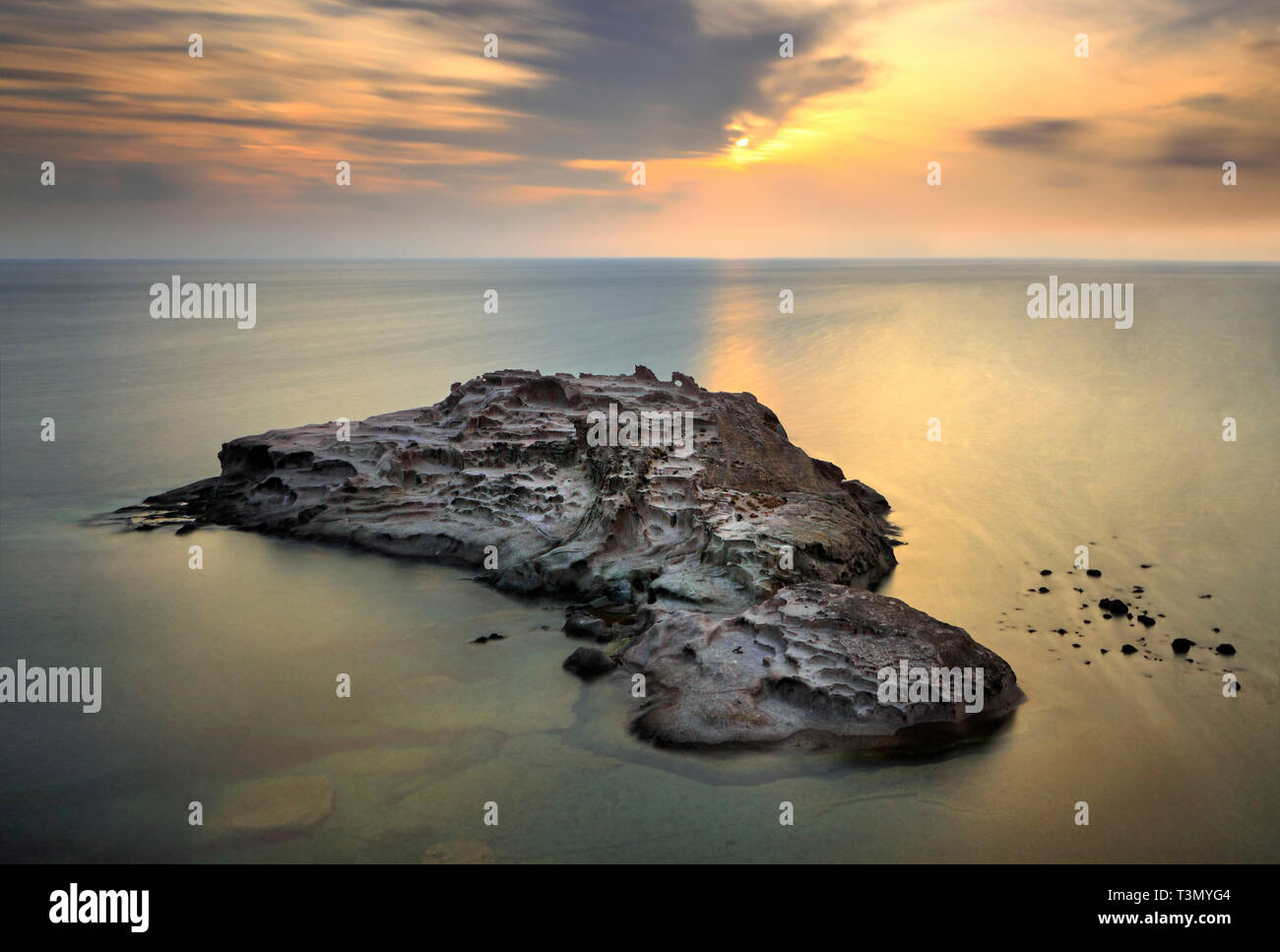 A small island just off the rocky coast of Torre Argentina, not far from Bosa in Sardinia, Italy. Taken on an evening of mid September 90 seconds of e - Stock Image