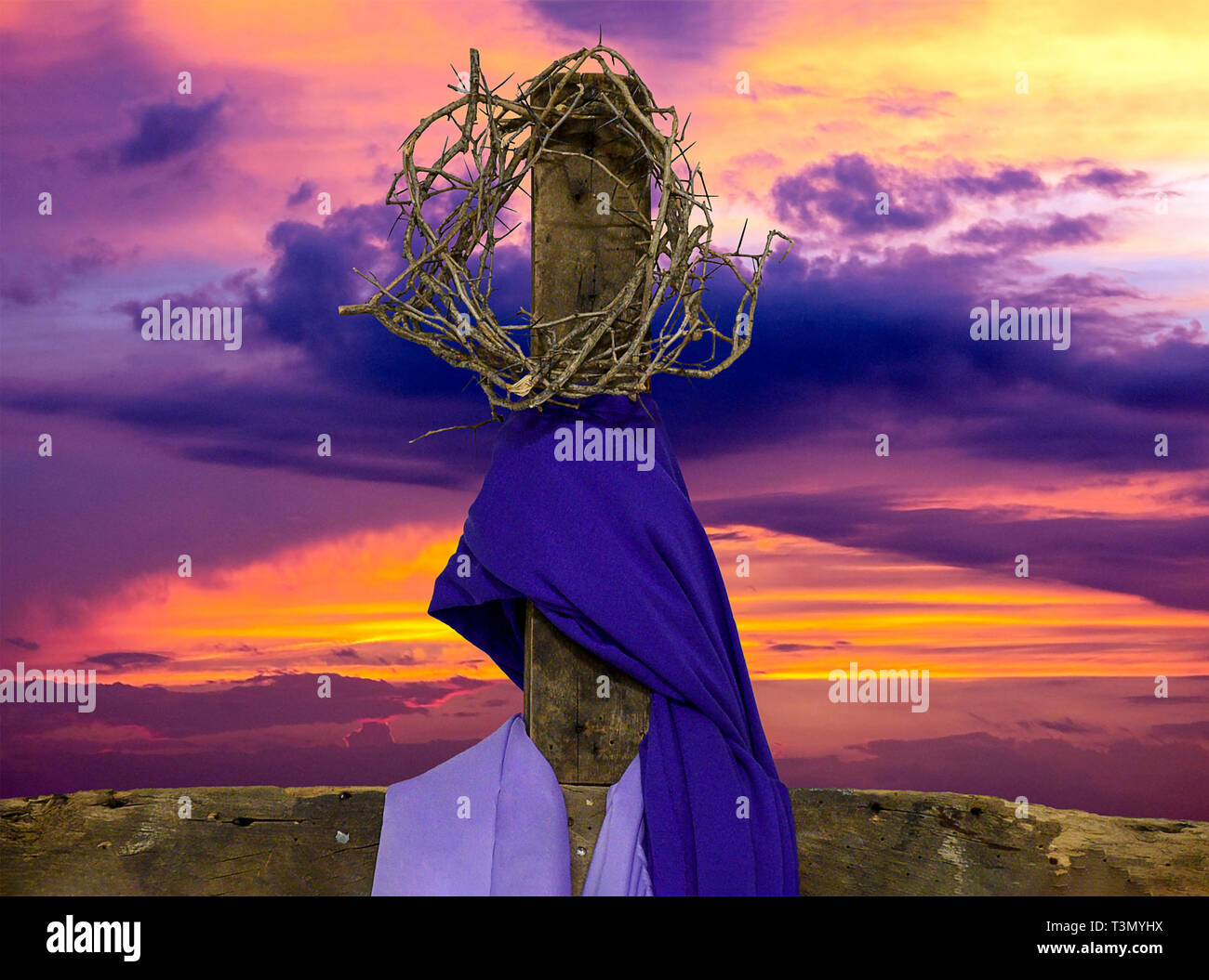 crown of thorns on rugged wooden cross with purple fabric drape and sunrise sky - Stock Image