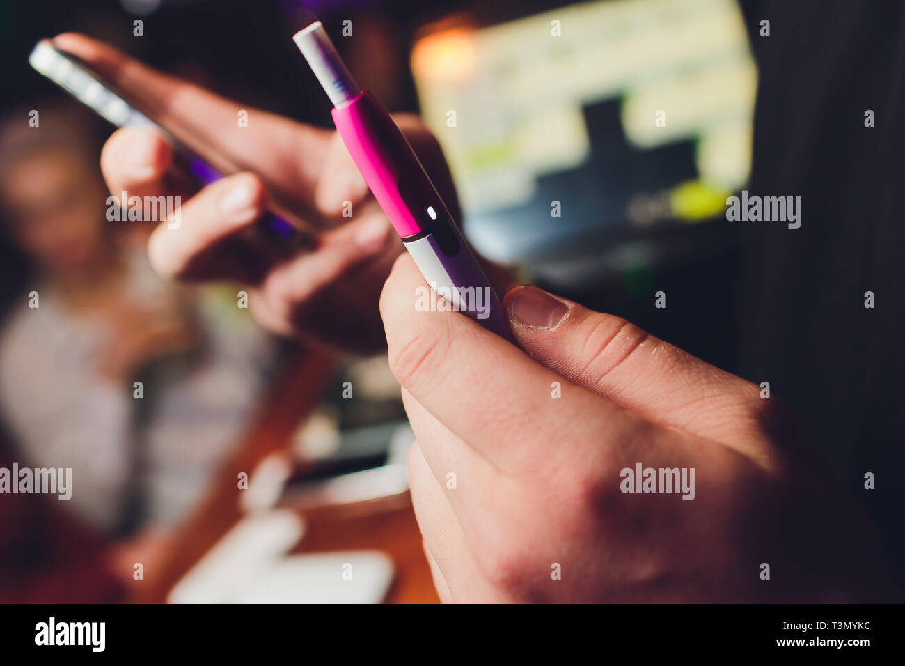 IQOS heat-not-burn tobacco product technology. Woman holding e-cigarette in his hand before smoking - Stock Image