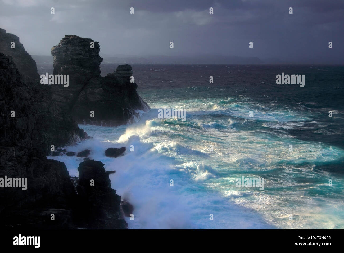 The rocky coast of Capo Falcone during a storm. Capo Falcone is a rocky promontory at the north-western tip of Sardinia, Italy, right in face of the I - Stock Image