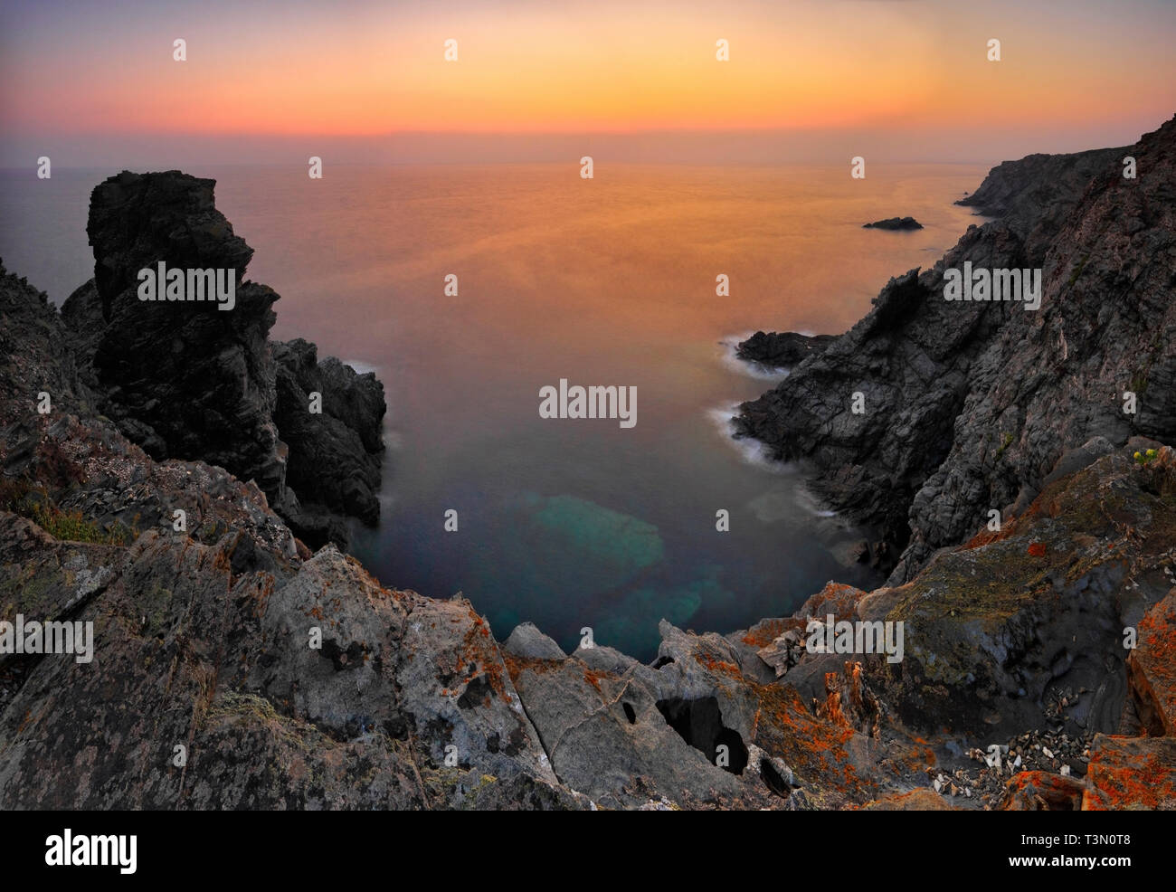 The rocky coast of Capo Falcone at sunset. Capo Falcone is a rocky promontory at the north-western tip of Sardinia, Italy, right in face of the Island - Stock Image