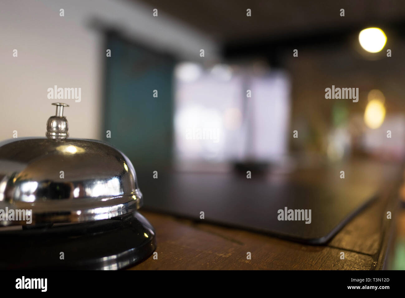 Service bell locating at reception. Silver call bell on table, receptionists on background. - Stock Image