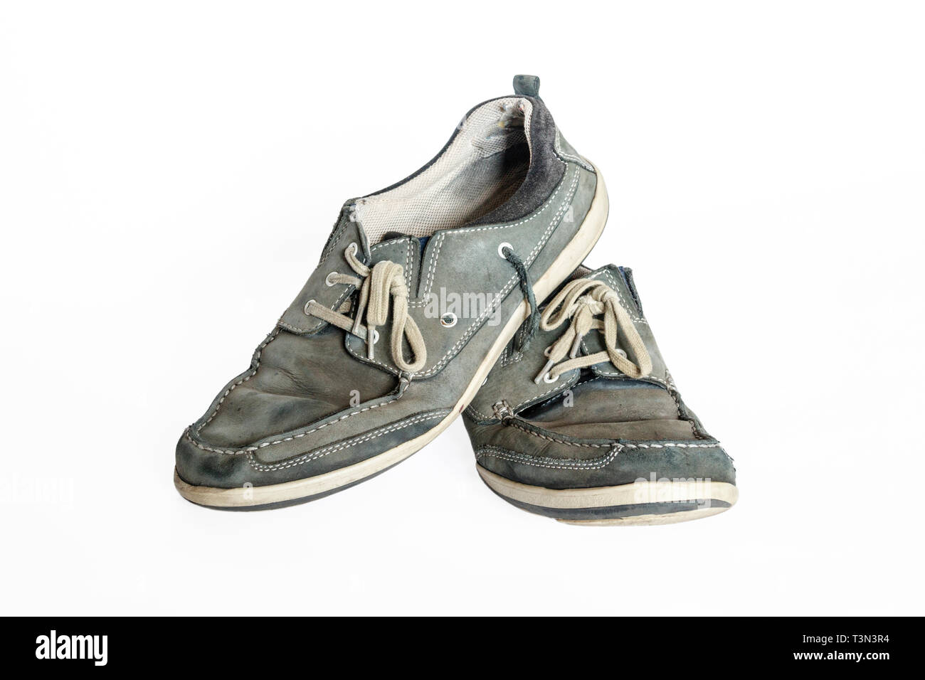 Close-up of pair of old worn-out blue-grey suede leather lace-up shoes isolated against a white background - Stock Image