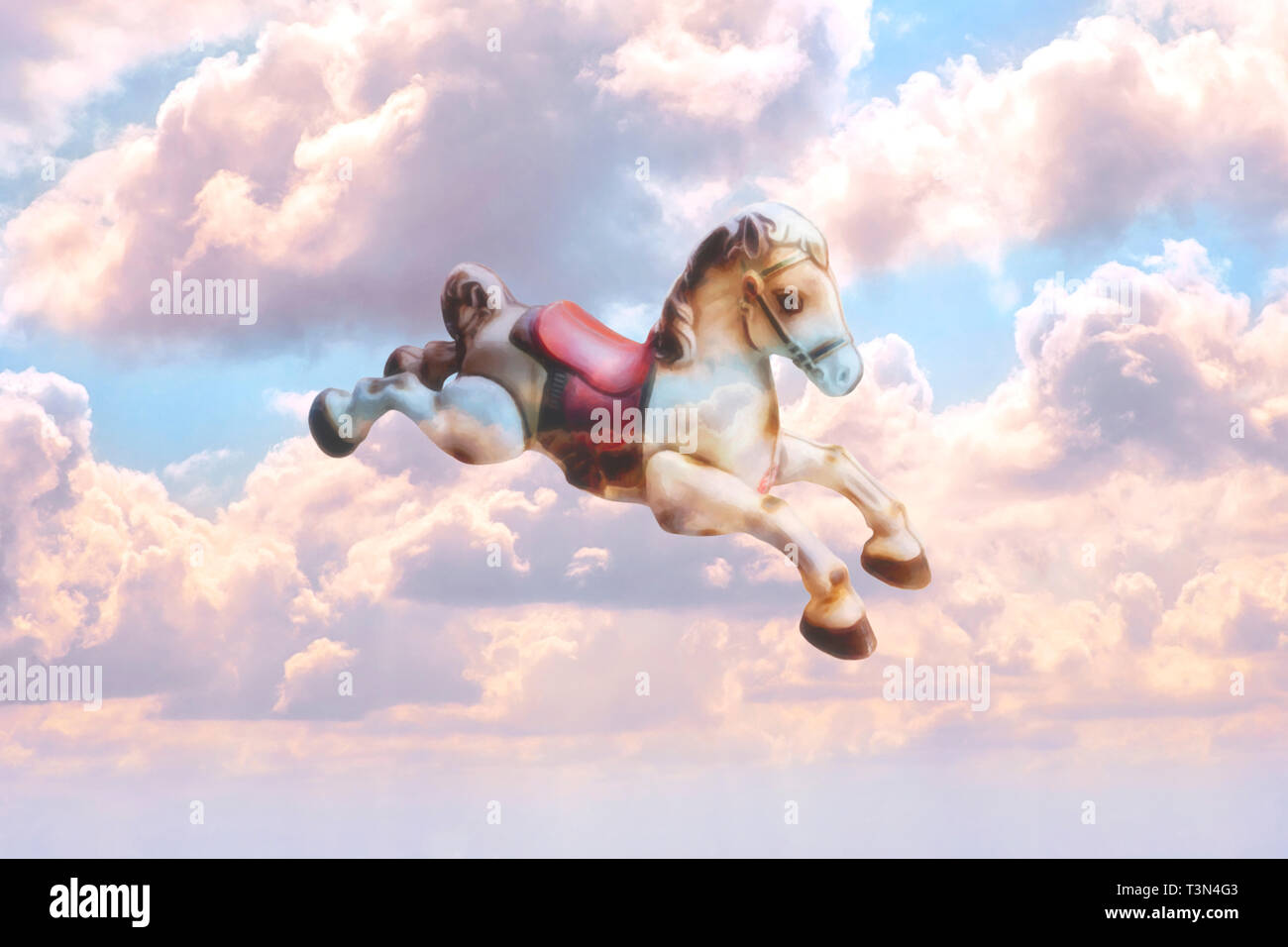 Concept image of an old-fashioned toy rocking horse flying through the sky, the pink clouds reflecting on its body Stock Photo