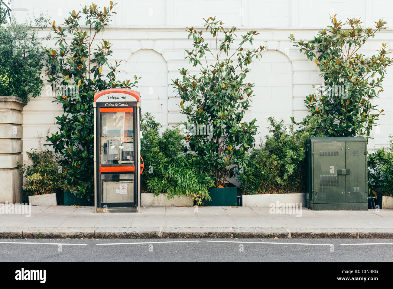 Telephone Box and green transformer box on Kensington Park Road in Notting Hill, London, UK - Stock Image