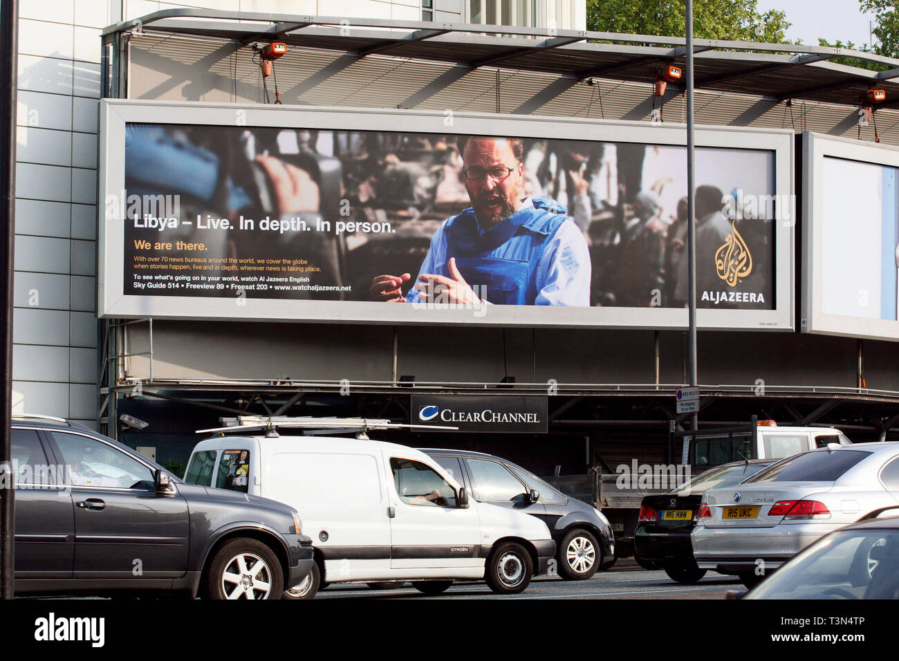 Al Jazeera news advert showing a war reporter wearing a bullet proof jacket presenting to camera in Libya. Cromwell Road, London. 6.5.11. - Stock Image