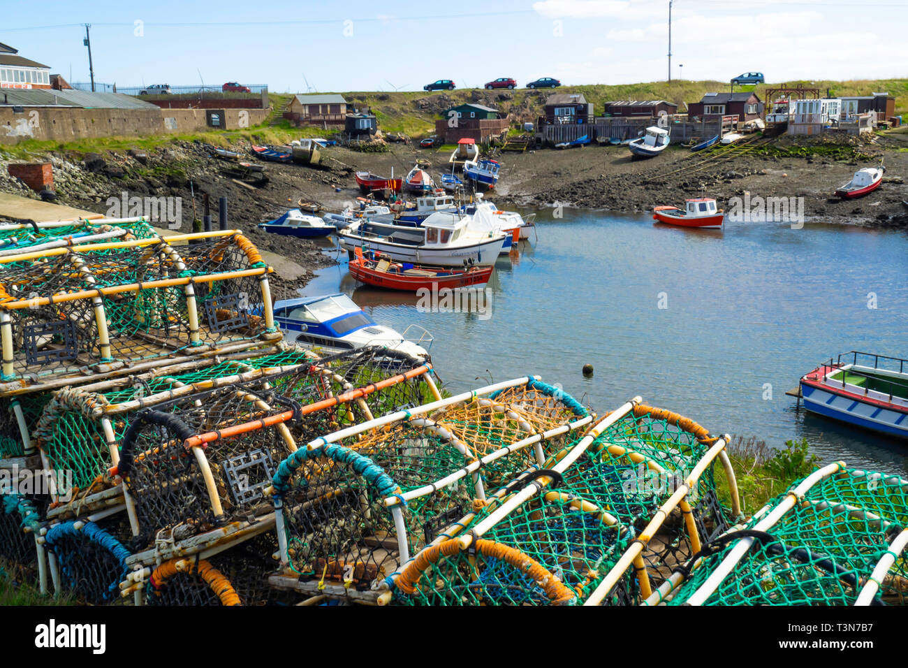 Fishing boats aground at low tide in Paddys Hole Harbour, on a spring day with traditional lobster or crab pots in the foreground at Teesmouth Redcar Stock Photo