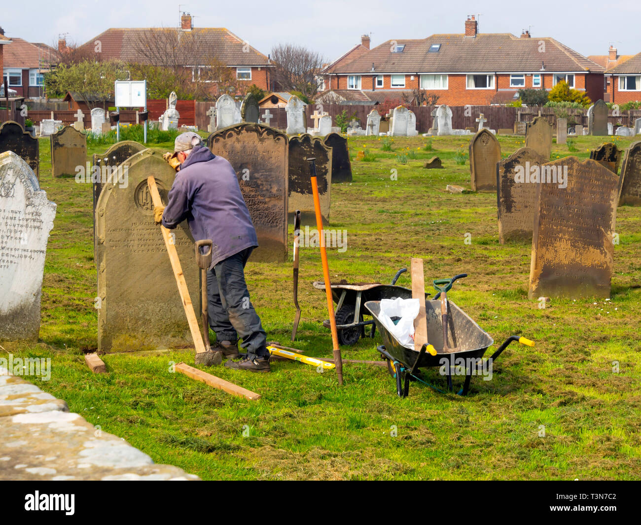 A stonemason at work re-erecting a fallen gravestone in the cemetery at St Germains Churcyard Marske by the Sea  North Yorkshire England UK Stock Photo