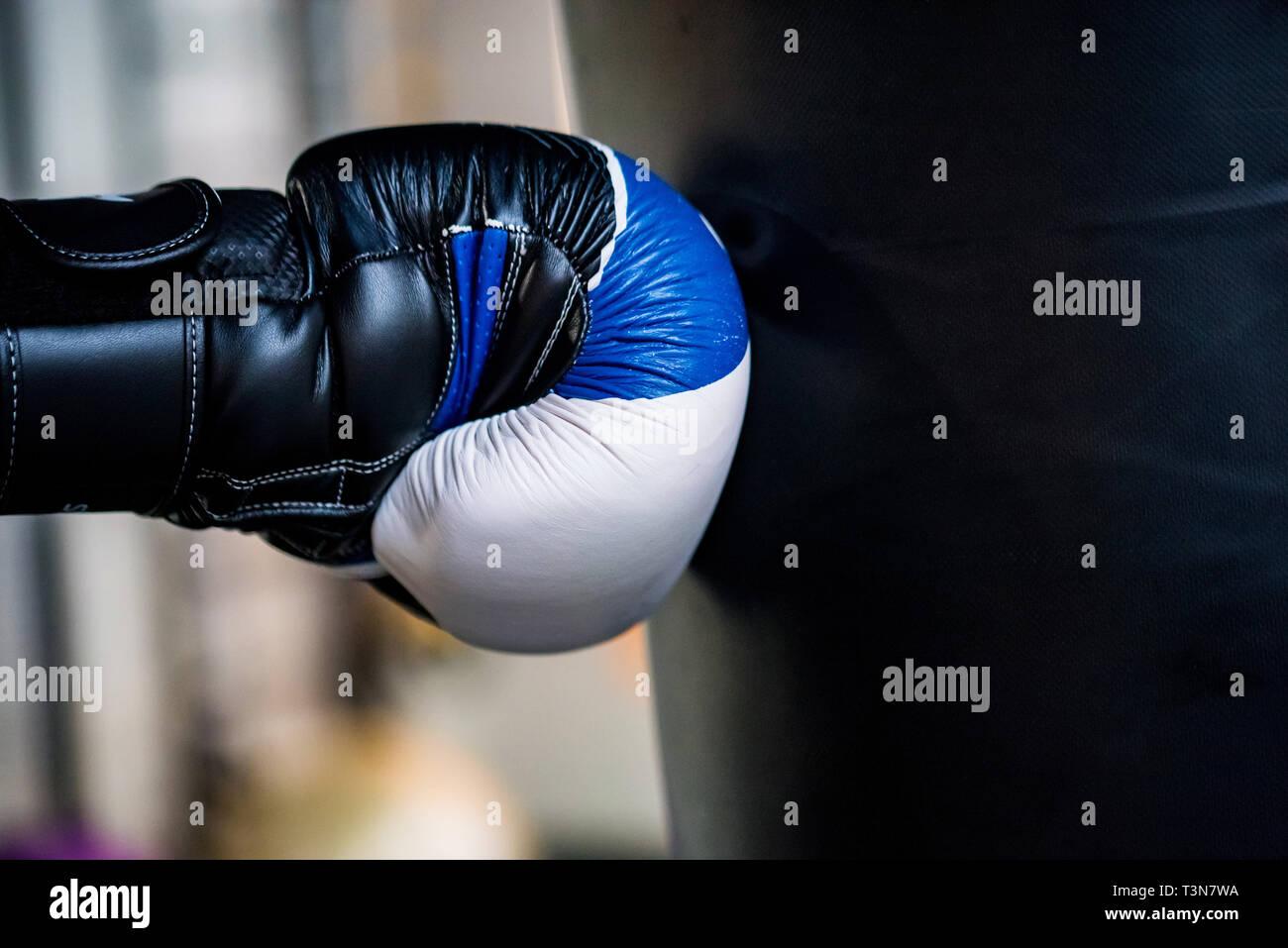 Boxing concept. Hand of boxer in glove hits black sandbag c Stock Photo