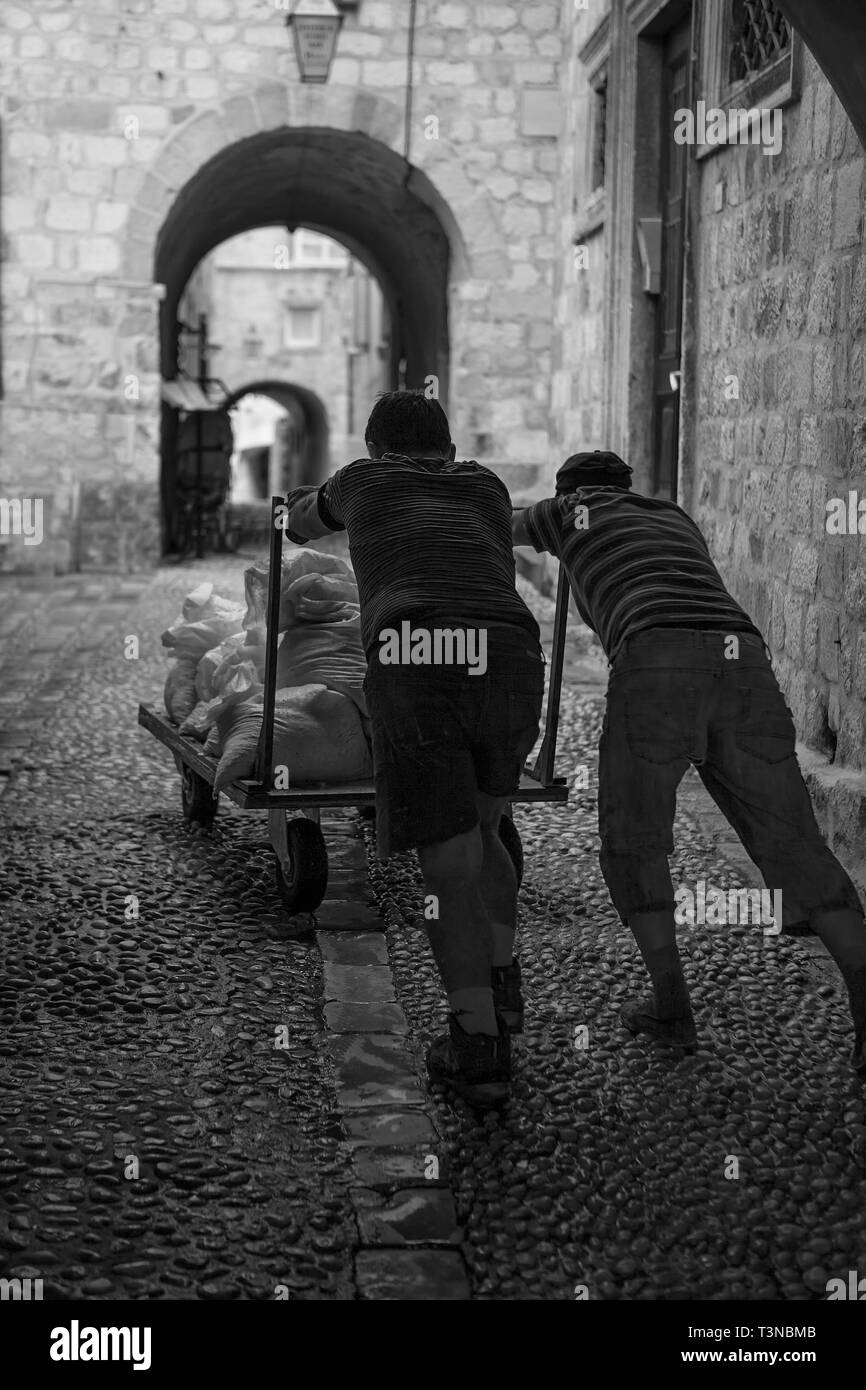 Ulica od Pustijerne, stari grad, Dubrovnik, Croatia: building materials being delivered by hand-cart down a cobbled lane.  Black and white version - Stock Image