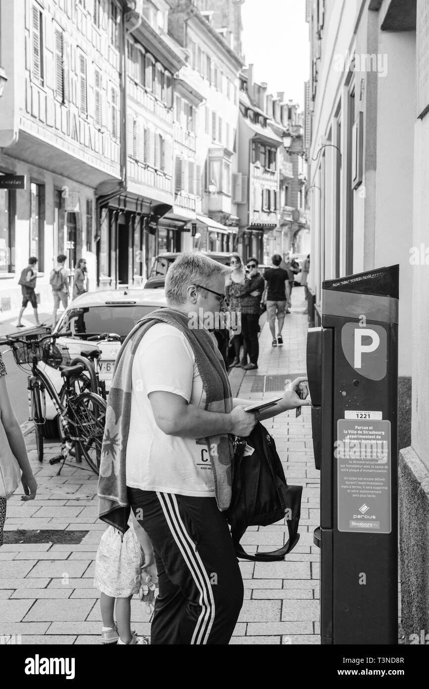 Strasbourg, France - Jul 22, 2017: man paying for parking in cetral Strasbourg at the parking meter with Notre-Dame cathedral in the background and shoppers on the Rue des Juifs black and white - Stock Image
