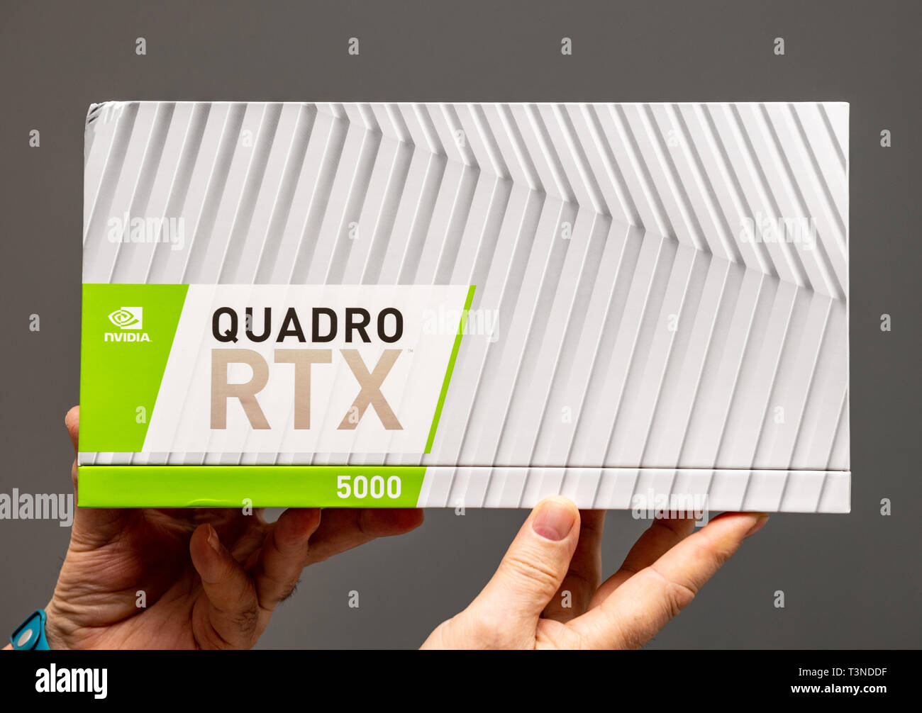 Paris; France - Mar 28 2019: Senior man showing cardboard packaging before unboxing of Nvidia Quadro RTX 5000 workstation GPU featuring new streaming multiprocessors; tensor cores - gray background - Stock Image