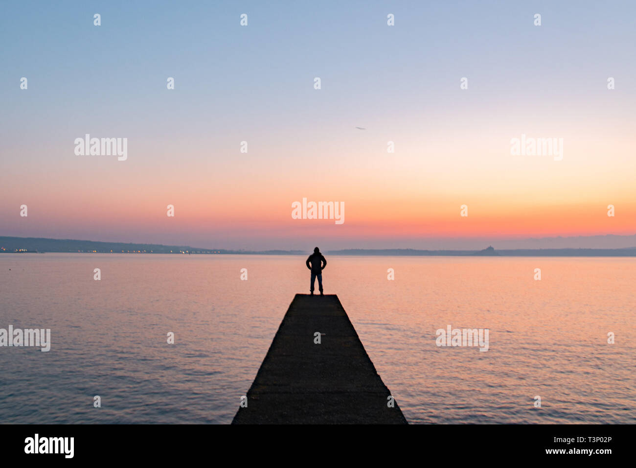 Man silhouetted standing on breakwater which extends out to sea at sunrise Stock Photo