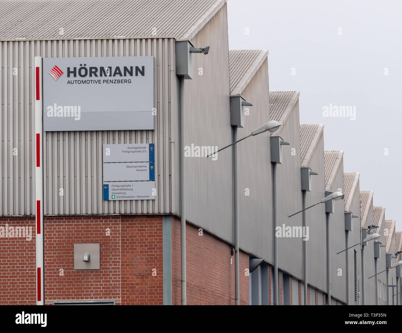 Penzberg, Germany. 11th Apr, 2019. A sign with the inscription 'Hörmann - Automotive Penzberg' hangs on the facade of the factory buildings. The Penzberg plant of Automotive Hörmann, the largest division of Hörmann Industries, is to be closed by June 30, 2020. Credit: Peter Kneffel/dpa/Alamy Live News - Stock Image