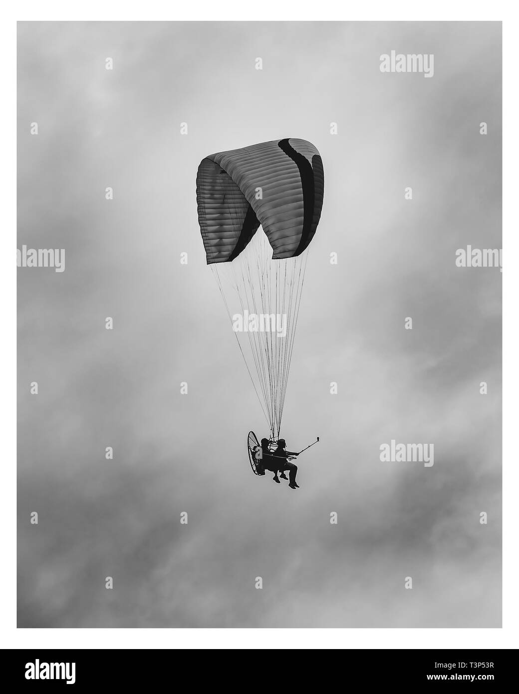 Flying on a motor paragliding. Tourist being guided on a flight with a powered paragliding on a cloudy day. Tourist holding a action camera. Black and - Stock Image