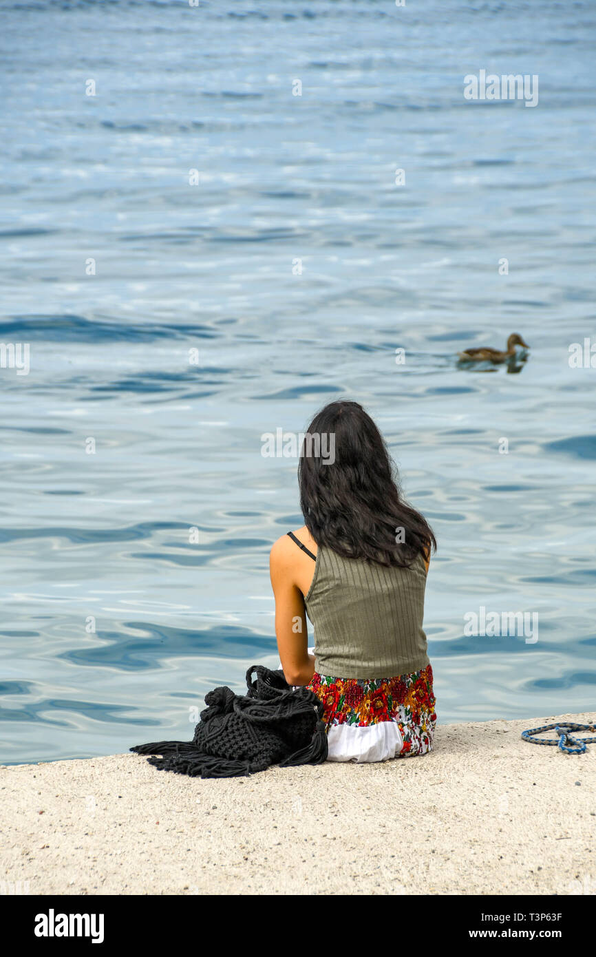 LAKE GARDA, ITALY - SEPTEMBER 2018: Young person sitting down on the edge of Lake Garda looking out over the calm water. - Stock Image