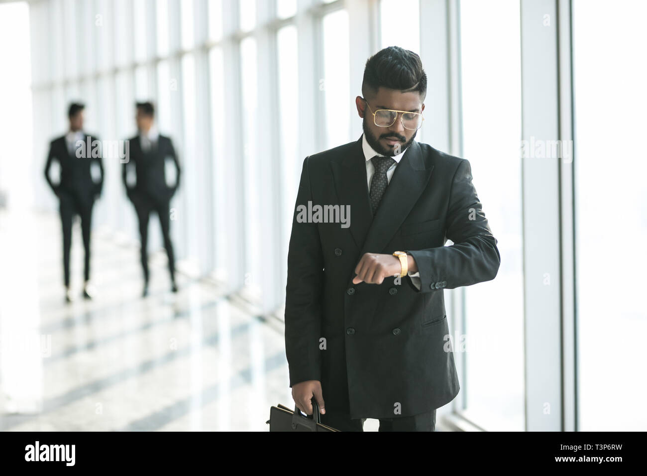 Busy Businessman Looking At Wristwatch While Hurrying On