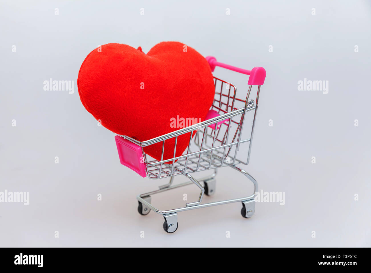 Sale buy mall market shop consumer concept. Simply minimal design with small supermarket grocery push cart for shopping toy with wheels and heart isol - Stock Image