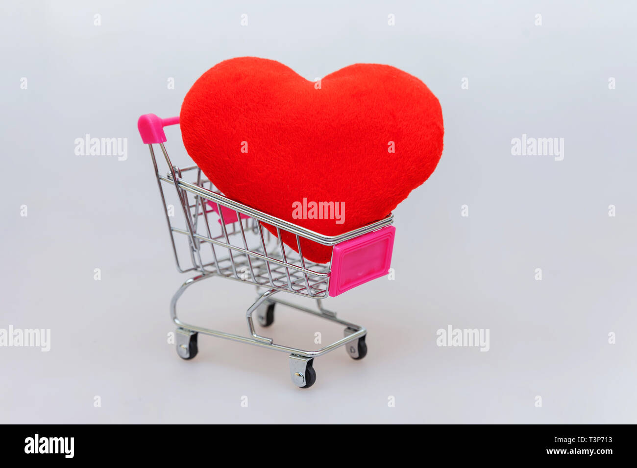Sale buy mall market shop consumer concept. Simply minimal design with small supermarket grocery push cart for shopping toy with wheels and heart isol Stock Photo